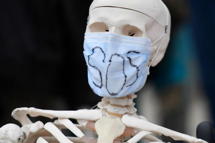"""Un esqueleto falso con una máscara que lleva la leyenda """"SOS""""."""