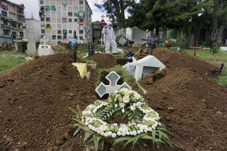 Sepultureros vestidos con trajes de bioseguridad cavan una tumba para enterrar el ataúd de una víctima del COVID-19 en el cementerio municipal de Mixco, Guatemala.