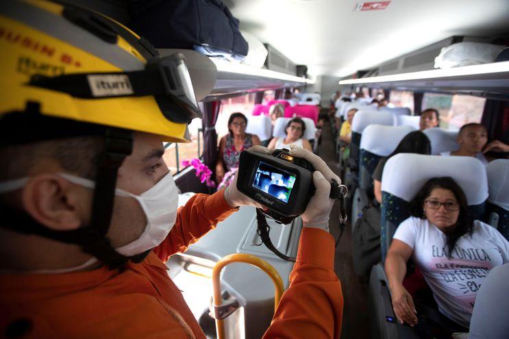 Bomberos usan cámaras térmicas y termómetros digitales para revisar a la ciudadanía mientras hacen un recorrido por los autobuses que llegan desde Sao Paulo este jueves a Brasilia (Brasil).