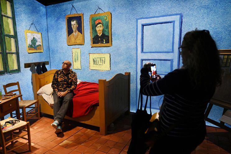 Un visitante interactúa con la recreación de la cama del pintor Vincent Van Gogh.