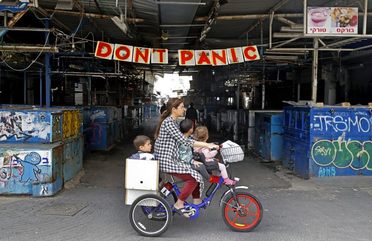 Una mujer monta una bicicleta con sus hijos frente a una pancarta colgada en la entrada del mercado Shuk HaCarmel (Caramelo) en la ciudad costera israelí de Tel Aviv.
