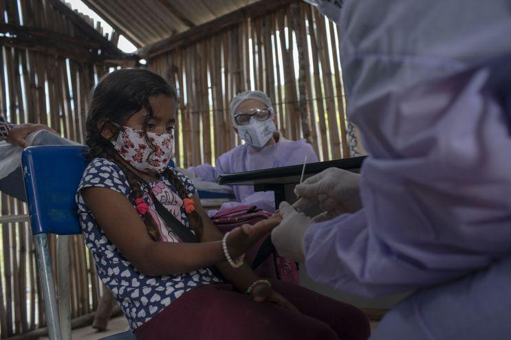 Un profesional de la salud administra una prueba COVID-19 a una niña indígena guaraní en un puesto indígena de atención médica en el campamento de la tribu Sao Mata Verde Bonita, en tierra indígena guaraní, en Marica, estado de Río de Janeiro, Brasil.