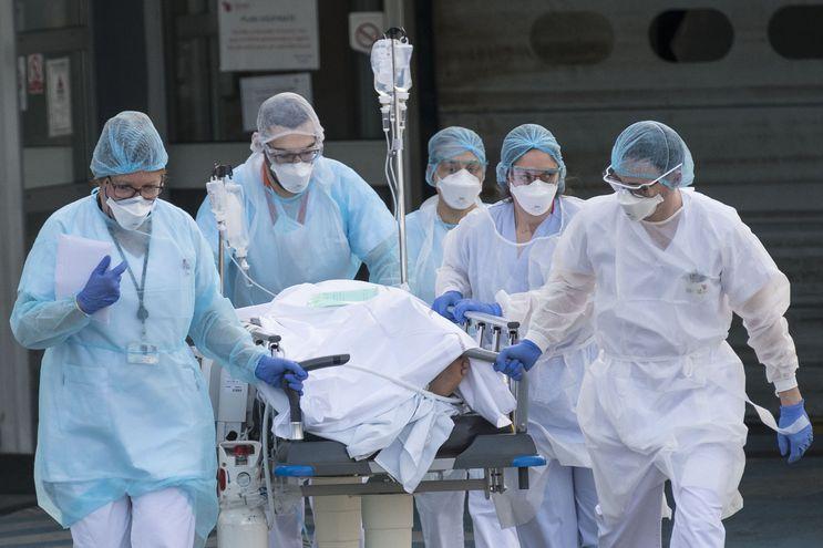 Médicos y enfermeros trasladan en camilla a un enfermo de coronavirus.