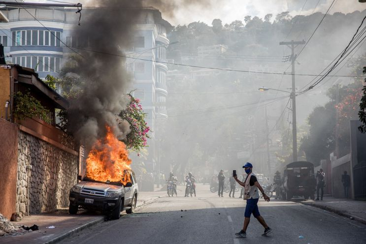 A car burns as demonstrators march in Port-au-Prince on February 14, 2021, to protest against the government of President Jovenel Moise. - Several thousand people demonstrated Sunday in the Haitian capital Port-au-Prince, saying the government was trying to establish a new dictatorship and denouncing international support for President Jovenel Moise. The protests were mostly peaceful, although a few clashes broke out between some demonstrators and police, who fired tear gas and rubber bullets. (Photo by Valerie Baeriswyl / AFP)