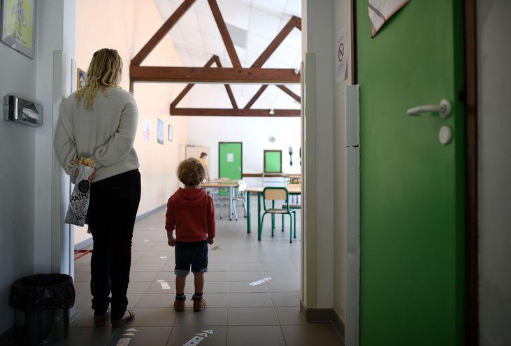 Una madre acompaña a su hijo al salón de clases donde los muebles fueron reacomodados para mantener distancia.