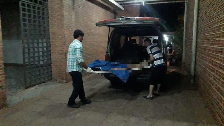 Funcionarios de una funeraria retiran el cuerpo de la mujer de la morgue del Hospital Regional de Concepción.