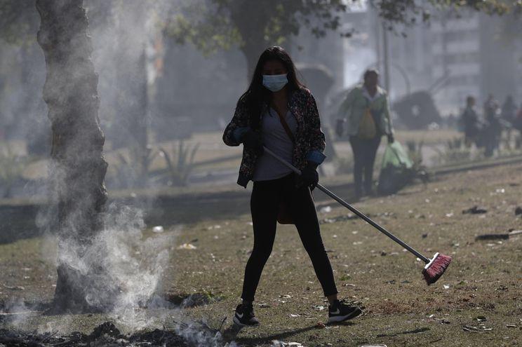 Un grupo de personas usa mascarillas sanitarias en las labores de limpieza de los escombros dejados por los disturbios en Quito.