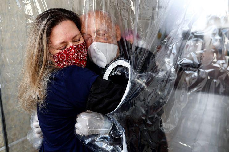 """Una mujer abraza hoy a su padre, que vive en una residencia de ancianos en la ciudad de Sao Paulo, a través de una """"cortina de abrazos"""", una alternativa válida para amenizar las medidas de distanciamiento social."""