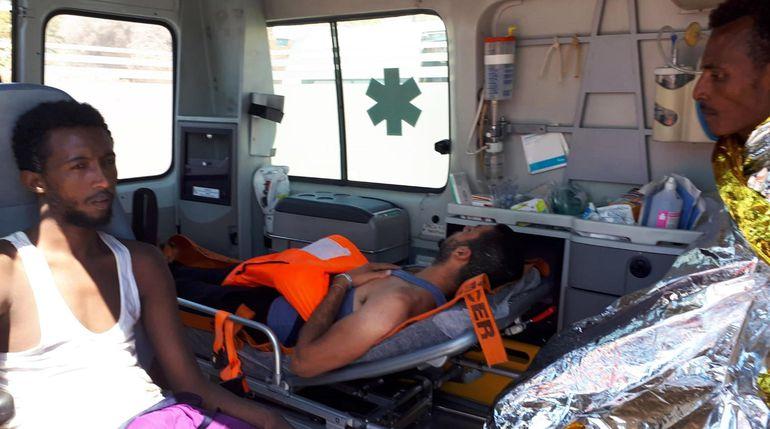 Dos de los migrantes que se arrojaron al mar desde el barco en un intento de llegar a la costa son atendidos en una ambulancia.
