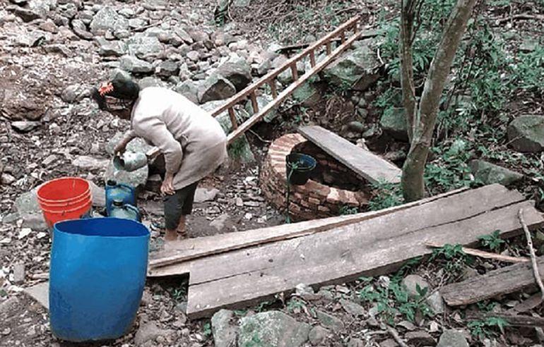 Una mujer carga en un bidón el agua  sacada de un aljibe.  Las fuentes  se están secando en Yarigua'a y otras comunidades rurales.