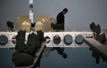 Un visitante pasa junto a una maqueta de la envoltura del Pont Neuf que había realizado el artista búlgaro Christo en París.