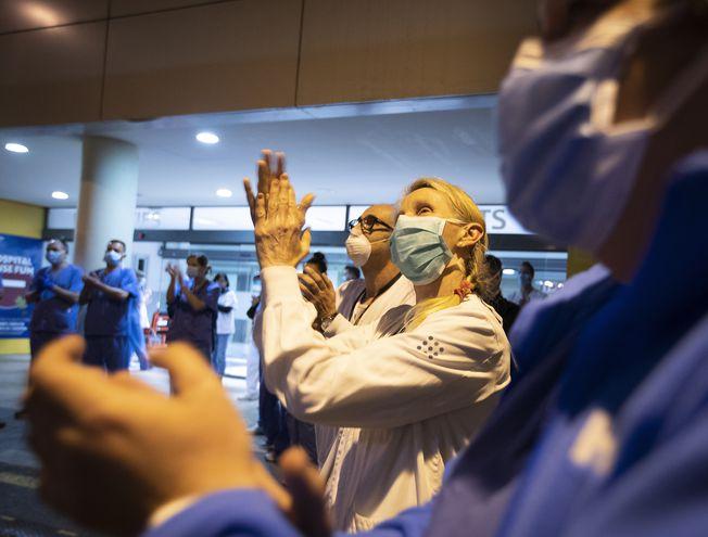 Trabajadores de salud españoles aplauden ante vítores de una multitud fuera del hospital Son Espases, en Palma de Mallorca.