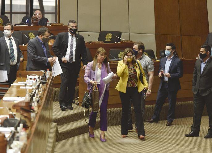 La diputada liberal  Celeste Amarilla (i) se retira con sus colegas de la oposición en protesta por el atropello al Estado de derecho.