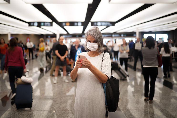 Pasajeros y empleados del Aeropuerto de Ezeiza, en Buenos Aires, se protejen con tapabocas.
