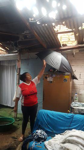 Una mujer muestra cómo quedó el techo de su casa tras el temporal de esta madrugada