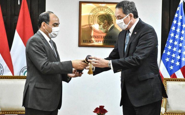 El canciller Antonio Rivas (izq.) entrega la condecoración al saliente embajador  Lee McClenny, por término de misión.