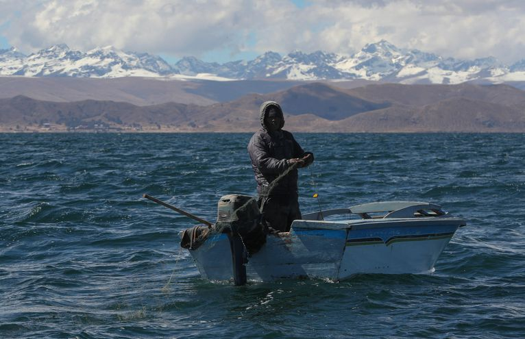 Un pesacador en la Bahía de Cohana el 22 de julio de 2019 en el lago Titicaca (Bolivia). El lago más grande a mayor altura en el mundo guarda en sus aguas leyendas que se remontan al imperio inca, pero también un enemigo silencioso: la contaminación, que avanza al extremo de convertir las aguas azules en oscuras y pestilentes en algunas zonas del Titicaca.