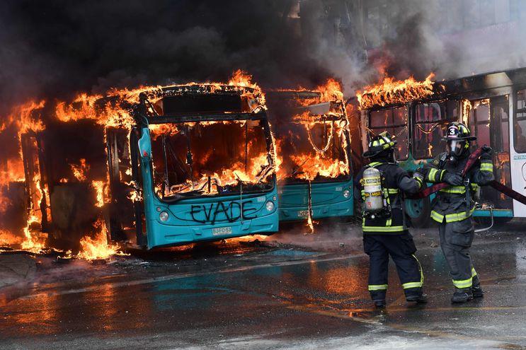 Bomberos intentan extinguir las llamas que consumen a varios buses luego de un enfrentamiento entre policías y manifestantes en Santiago, el sábado.
