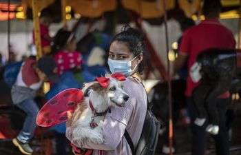 A woman carries her dog to be blessed by Saint Lazarus, in Monimbo neighbourhood in Masaya, about 35 km south of Managua, on March 21, 2021. - According to tradition in Nicaragua, faithfuls ask Saint Lazarus for the health of their dogs and pay these favours back by bringing their pets dressed in costumes to attend mass in honour of the saint. (Photo by Inti OCON / AFP)