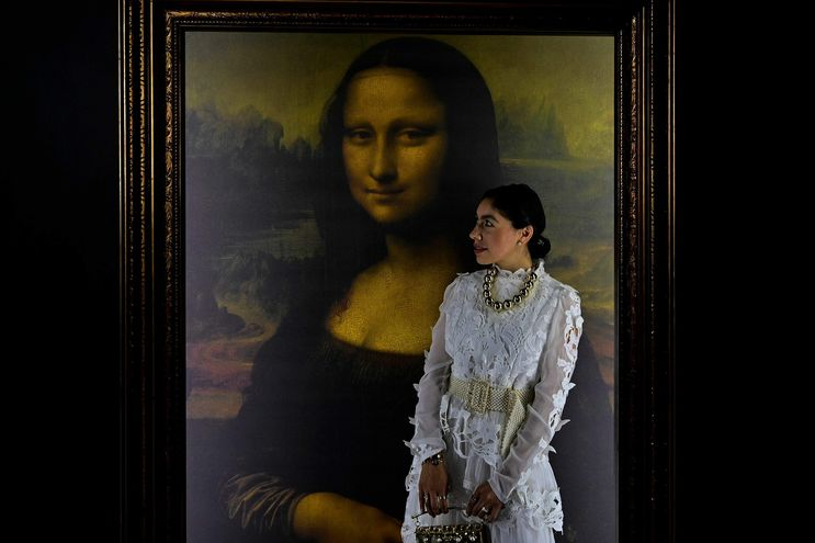 Una mujer posa junto al retrado de Lisa Gherardini, esposa de Francesco del Giocondo, conocida como la Mona Lisa o La Gioconda, en la exposición DaVinci Experience en Mexico.