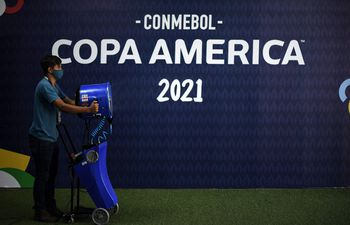 A Conmebol staff member performs cleaning and disinfection tasks ahead of the 2021 Copa America football match between Uruguay and Chile, at the Arena Pantanal in Cuiaba, Mato Grosso state, Brazil, on June 21, 2021. (Photo by DOUGLAS MAGNO / AFP)