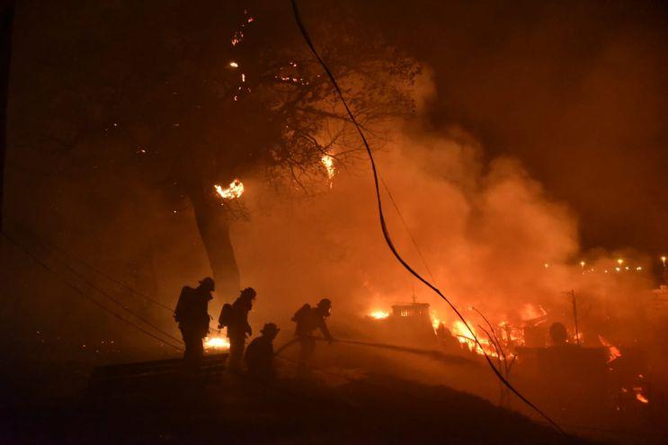 Bomberos trabajan arduamente para sofocar el fuego detrás del edificio del ex Cabildo.
