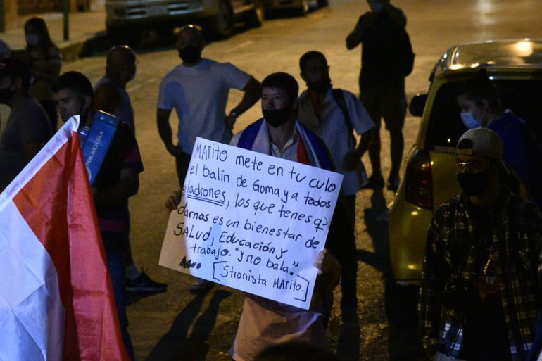 Un hombre sostiene un cartel en contra de la violencia policial en el sexto día de protestas contra el gobierno Mario Abdo, en el microcentro de Asunción, el miércoles 10 de marzo de 2021.