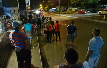 Pasajeros esperan colectivo en los alrededores de la Terminal de Ómnibus de Asunción, para retornar al hogar, durante una noche de regulada del transporte público.