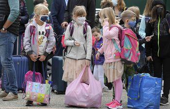 Alumnas con tapabacos forman fila para ingresar a la escuela en Estrasburgo, Francia.