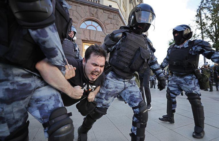 Policías antidisturbios llevan detenido a uno de los manifestantes de la protesta en Moscú.