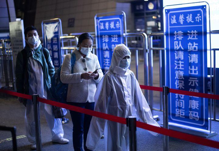 Personas con trajes de protección en una estación de trenes en Wuhan, China.