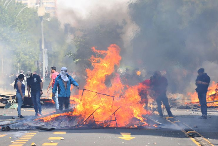 Manifestantes queman objetos durante una protesta contra el incremento del precio en los billetes del metro, este sábado en Santiago (Chile).