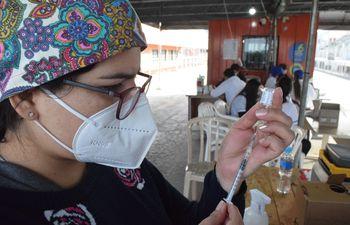Una vacunadora prepara una jeringa en el vacunatorio del centro cívico. Al fondo, el equipo de apoyo técnico.