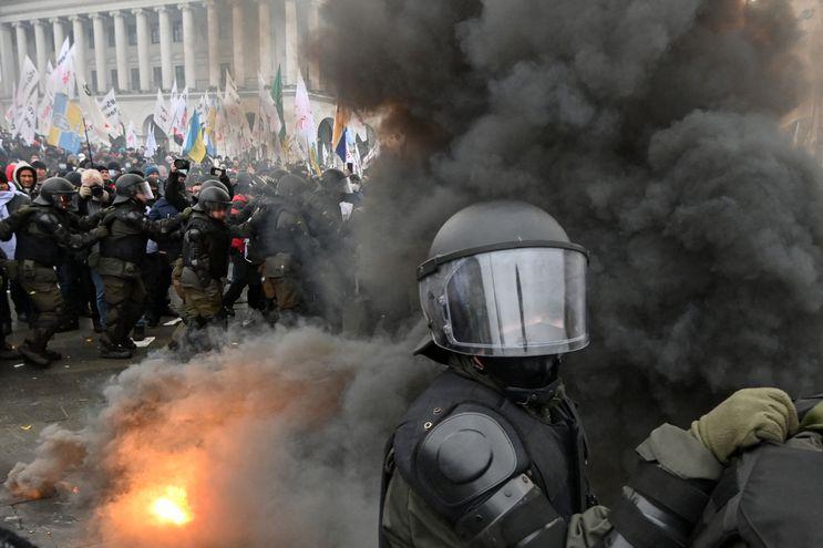 Policías antidisturbios y manifestantes que se oponen al confinamiento debido a la pandemia de covid-19 se enfrentan en Kiev, este martes.