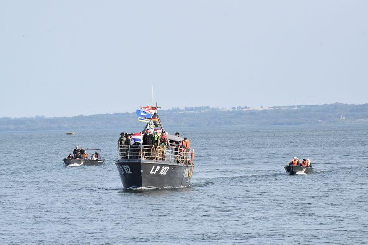 La procesión náutica a través del río Paraná a bordo de una patrullera de la Prefectura Naval de Itapúa, escoltada por embarcaciones menores, en el marco de un atractivo paisaje.