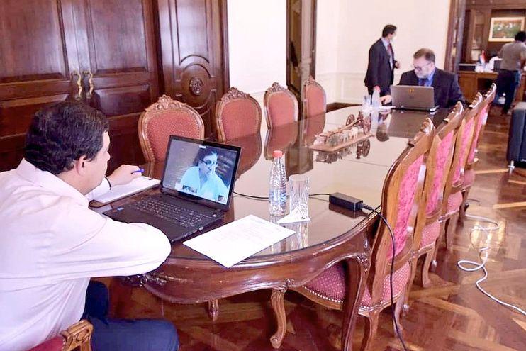 Hugo Velázquez (i) dialoga en videoconferencia con el titular del Senado, Blas Llano (PLRA). En el otro extremo de la mesa,  Benigno López conversa con el diputado liberal  Julio Mineur.