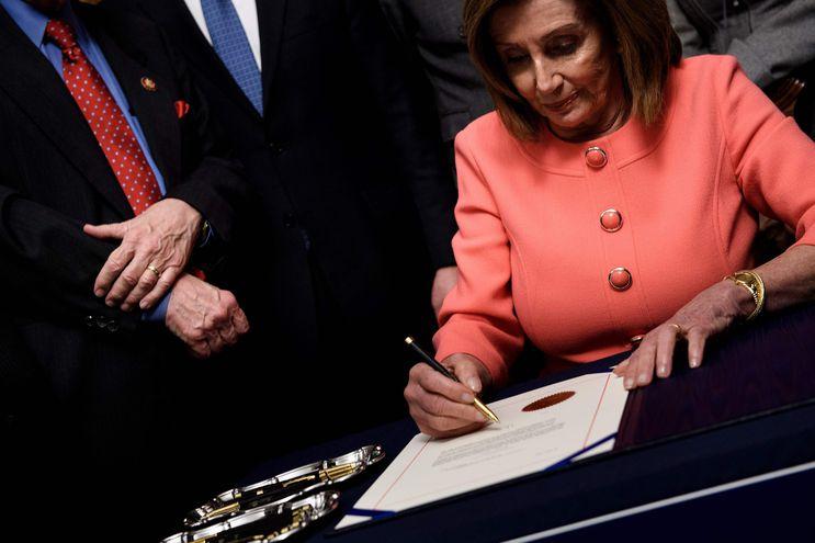 La presidenta demócrata de la Cámara  de Representantes, Nancy Pelosi, firma los artículos del juicio político al presidente del EE.UU., Donald Trump.