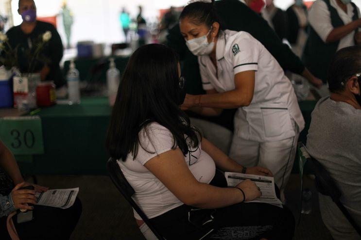Una embarazada recibe la dosis de la vacuna de Pfizer contra el COVID-19 en una escuela en Ciudad de México.