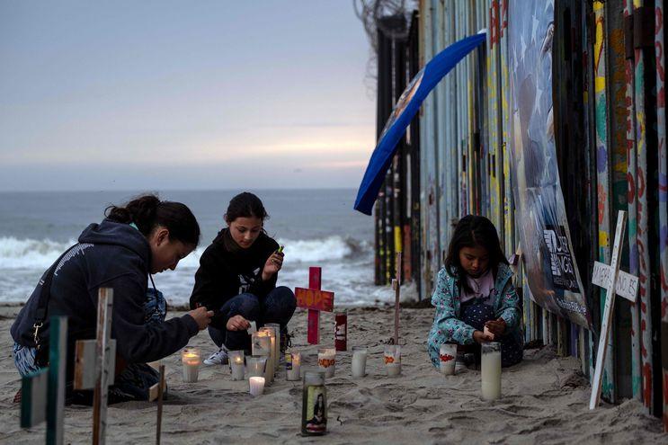 Tres personas encienden velas durante un evento en conmemoración de los fallecidos en su intento de cruzar a Estados Unidos en Playas de Tijuana, Baja California (México).