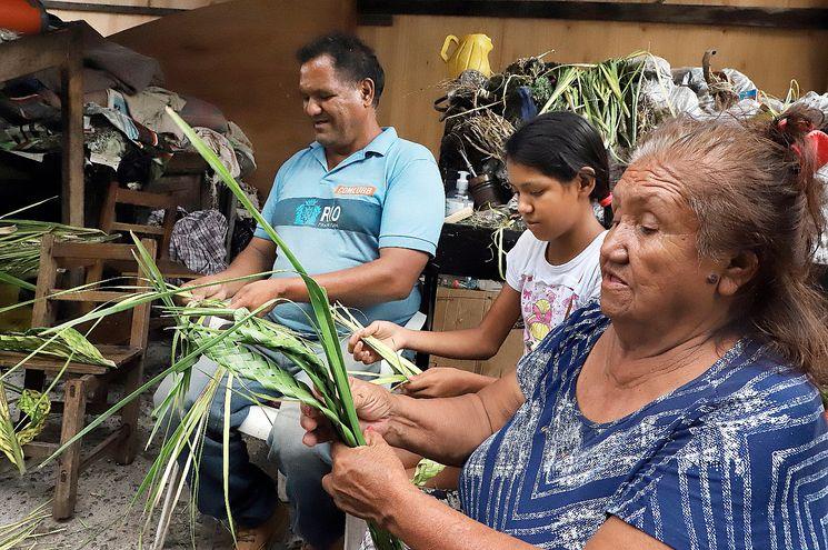 Tres generaciones. Alberto, Analía y Aparicia Torres trenzan sus palmas a vender en el Paseo de los yuyos.