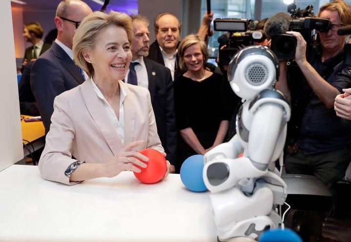 La presidenta de la Comisión Europea, Ursula von der Leyen, junto a un robot durante su visita al Centro Xperience de Inteligencia Artificial, este martes en Bélgica (Bruselas).
