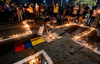 People place lit candles on the ground during a vigil on May 5, 2021 in Cali, Colombia, in honor of the demonstrators who died during protests against the government of President Ivan Duque. - Thousands of people returned to the streets of Colombia on May 5 in rejection of the government of Ivan Duque, who has completed a week of pressure with demonstrations that turned violent in some cities and left some twenty people dead. (Photo by Luis ROBAYO / AFP)
