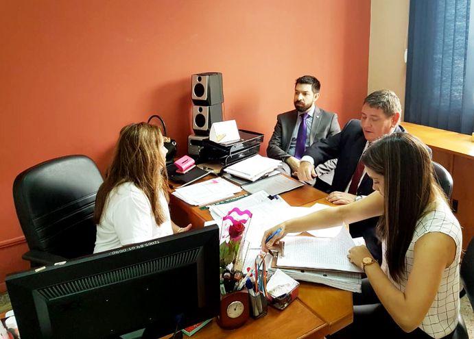 Los agentes fiscales Osmar Legal (izq.) y Federico Delfino piden los documentos del contrato a una funcionaria de la UOC.