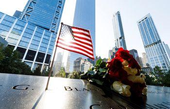 Flores y una bandera estadounidense sobre los nombres de los fallecidos en los ataques del 11 de septiembre de 2001, en el monumento dedicado a ese evento en Nueva York.