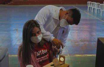 Una joven al momento de recibir su refuerzo contra el COVID-19 en un vacunatorio de Villarrica.