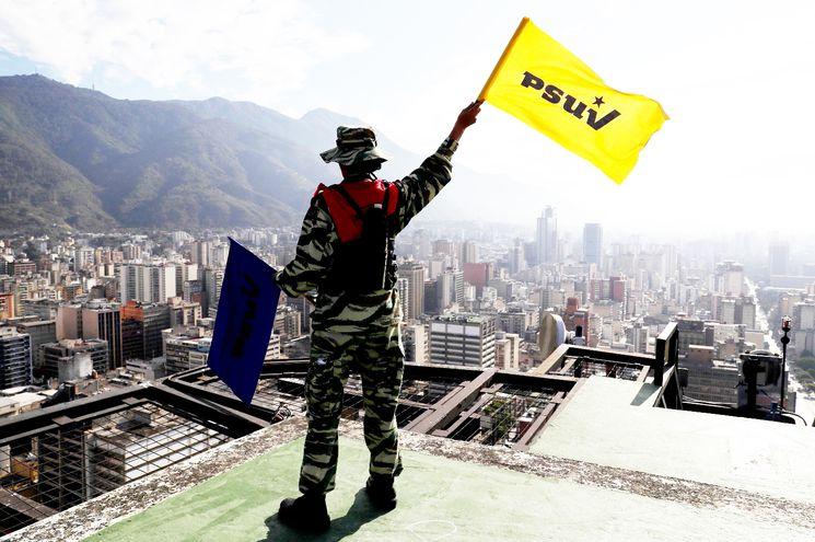 """Miembro de las Fuerzas Armadas venezolanas agita una bandera del partido oficialista venezolano (Partido Socialista Unido de Venezuela) en una de los """"ejercicios de defensa""""."""