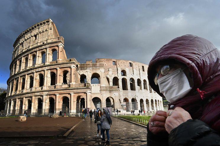 Un hombre con una máscara camina cerca del Coliseo romano.