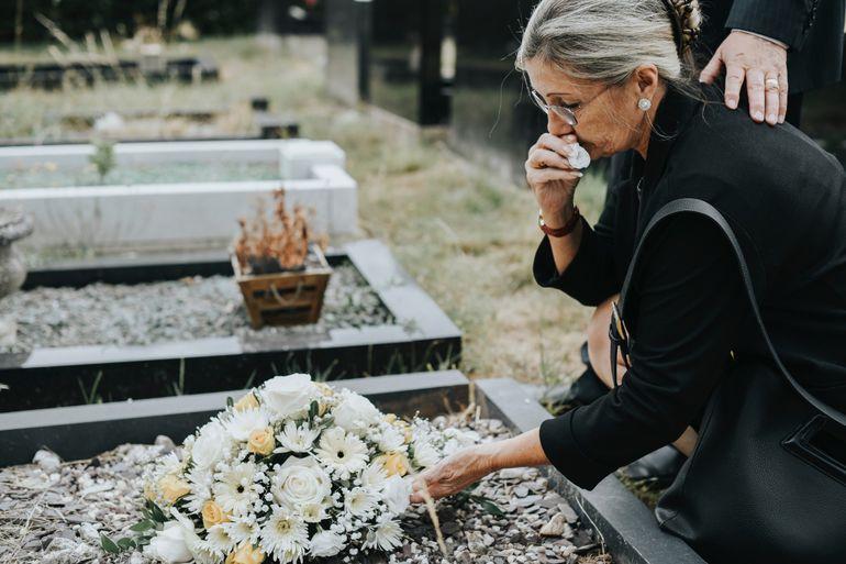 Mujer llora en eun cementerio.