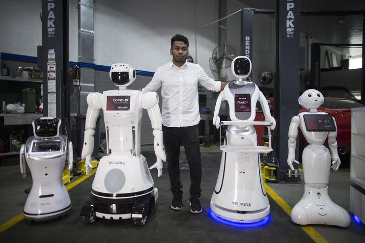 Aswin Sarang, directivo de Reliable Robotics, posa junto a robots que detectan fiebre e higieniza manos en Dubai, Emiratos Árabes Unidos.