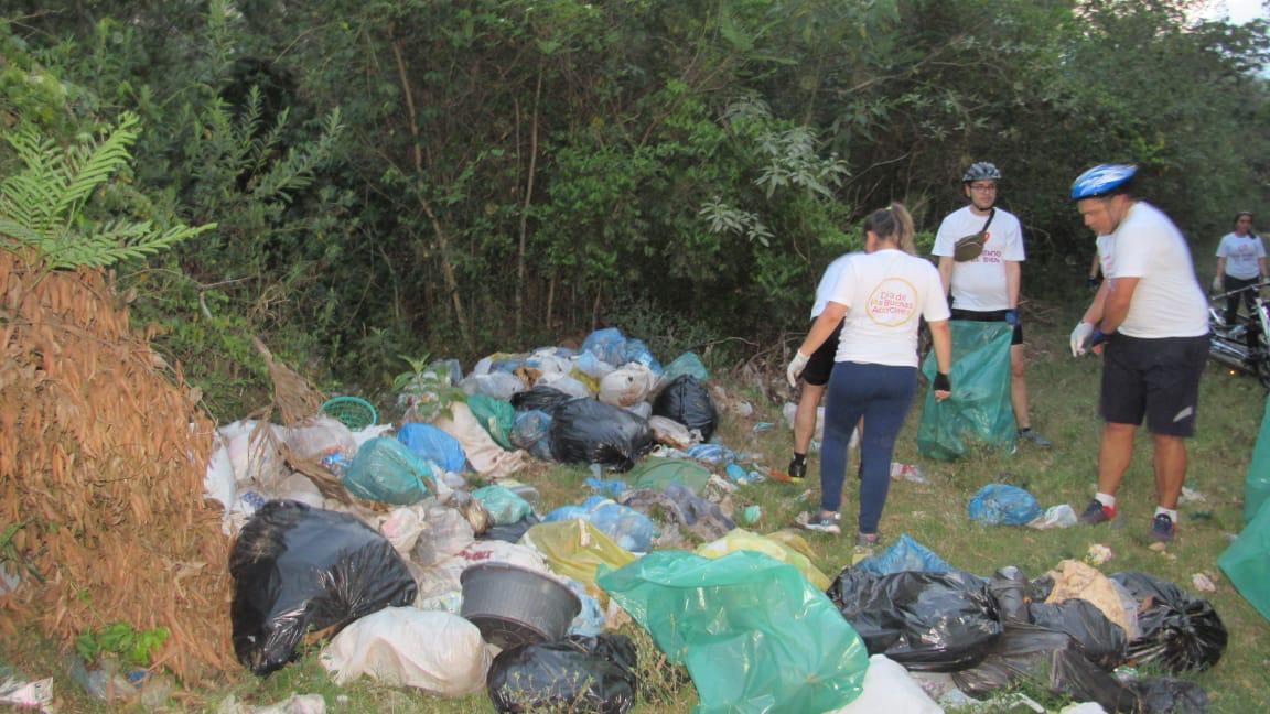 Los ciclistas recogiendo las basuras tiradas a los costados de la ruta